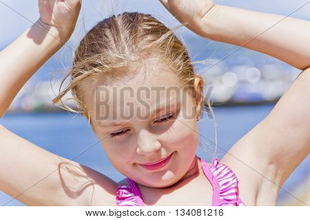 Portrait of dancing girl on the riverbank in pink swimsuit