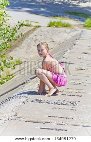 Cute jumping girl in pink swimsuit on the riverbank