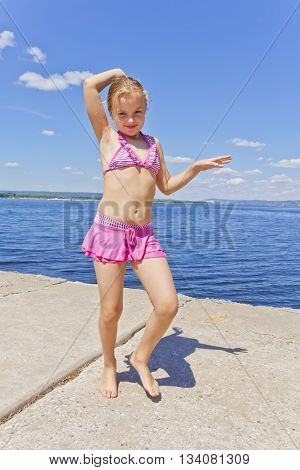 Dancing girl in pink swimsuit on the riverbank