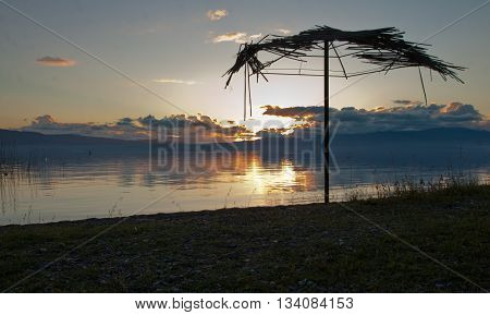 Reed umbrellas and sunbed beach on the purple sunset beach. Ohrid, Macedonia.