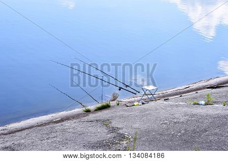 Chair with fishing poles and fishing equipment at the lake