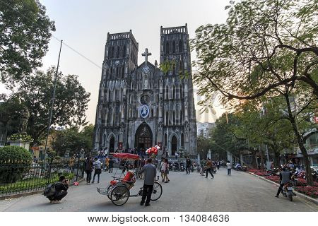 Hanoi Vietnam: February 21 2016: Tourists and local people walking in front of Saint Joseph Cathedral the most important church of Hanoi
