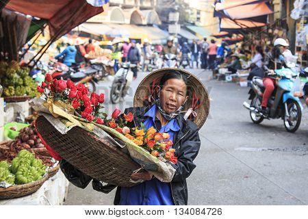 Hanoi Vietnam: February 21 2016: Womand selling flowers in Hoàn Kiếm the old quarter of Hanoi