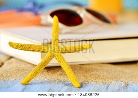 closeup of a yellow starfish on a pile of sand, and a pair of sunglasses on a book, placed on a rustic blue wooden surface