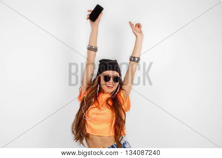 beautiful woman in sunglasses wearing in black hat and orange T-shirt listening music and dancing near white wall, holding a cell phone in hand, hands raised up, fashion concept