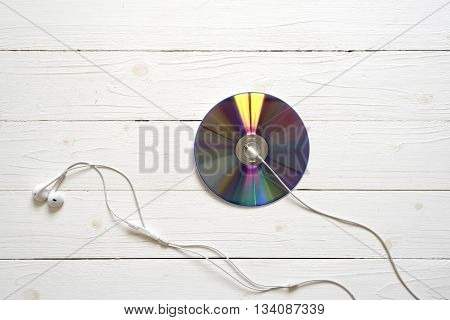 top view of dvd disk and earphone on wood white background