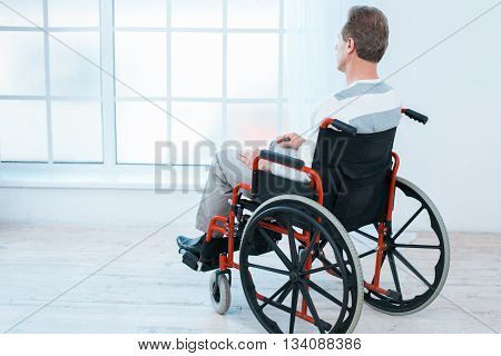 Adult man in wheelchair. White interior with big window. Sad man looking at window. Back view photo