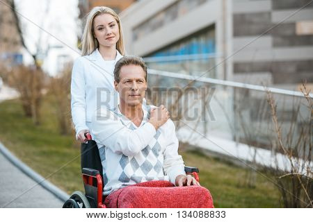 Adult man in wheelchair during walk. Man and young helper looking at camera. Nurse carrying patient on wheelchair