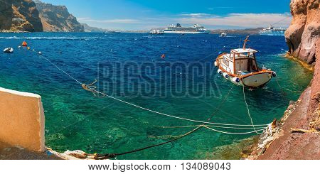 Fishing Boat, motor boats and cruise liners in Mesa Gialos, Old Port of Fira, Santorini, in the sunny day, Greece. Panorama