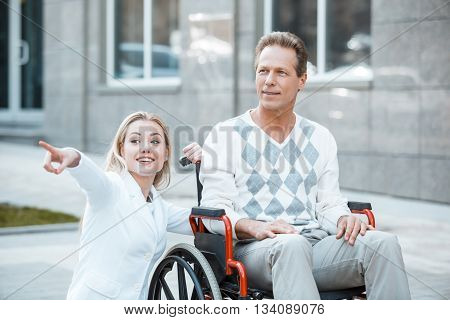 Adult man in wheelchair during walk. Nurse carrying patient on wheelchair
