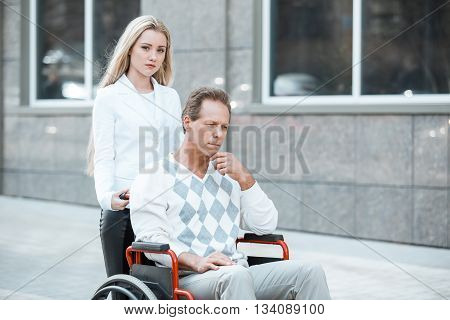 Adult man in wheelchair during walk. Sad man and young helper looking at camera. Nurse carrying patient on wheelchair