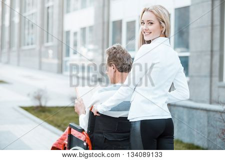 Adult man in wheelchair during walk. Young helper smiling and looking at camera. Nurse carrying patient on wheelchair. Back view photo