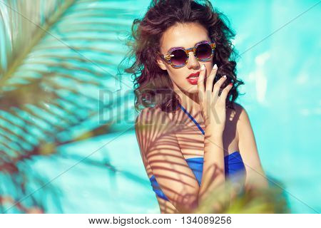 Summer beach style portrait a beautiful young woman wearing bikini and sunglasses under a palm tree