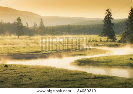 Gentle flowing fishing stream winding through meadow of golden lit summer sky with mist and steam