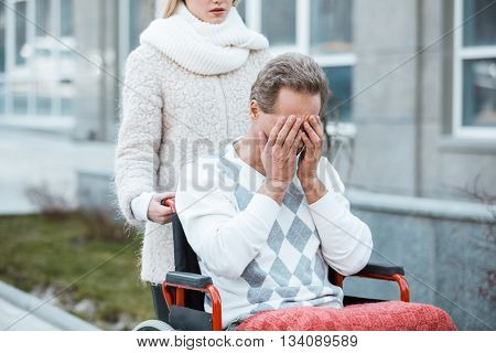 Adult man in wheelchair during walk. Nurse carrying sad patient on wheelchair. Man closing his eyes with hands