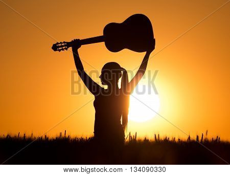 Girl With Guitar At Sunset