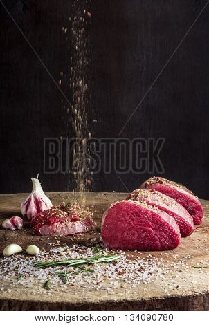 a juicy piece of meat lying on a wooden board. sprinkle with spices