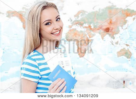 Travel concept. Portrait of stylish beautiful young woman near map as a background. Woman smiling, looking at camera and holding tickets with passport