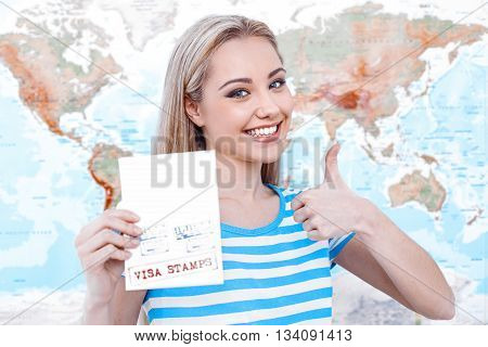 Travel concept. Portrait of stylish beautiful young woman near map as a background. Woman smiling, looking at camera, showing thumb up and holding passport with visa