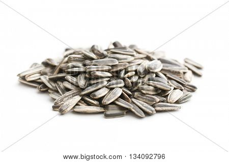 Unpeeled sunflower seeds isolated on white background. Sunflower seeds are healthy superfood.