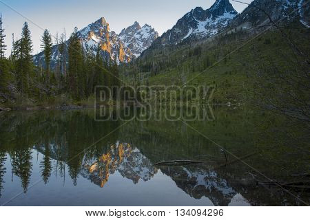 Beautiful mountain lake reflection of rugged rocky Teton snow capped mountain range blue sky majestic landscape scene