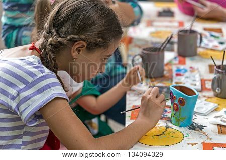 TIMISOARA ROMANIA - JUNE 1 2016: Girl who paints a ceramic vase. Workshop organized by the City Hall Timisoara with the occasion of the International children Day.