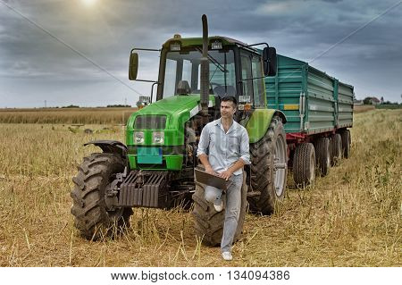 Farmer With Laptop Leaning On Tractor