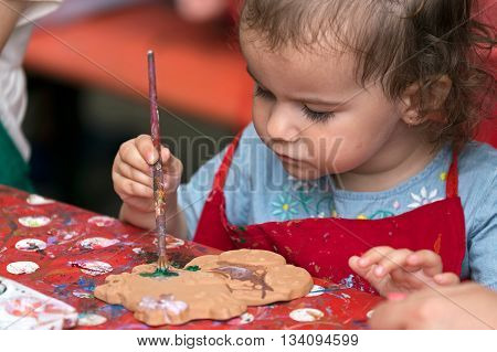 TIMISOARA ROMANIA - JUNE 1 2016: Little girl who paints a ceramic object. Workshop organized by the City Hall Timisoara with the occasion of the International children Day.