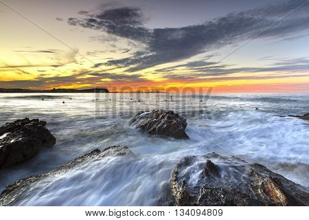 Currumbin Rock Gold Coast sunset with surfer silhouettes and ocean current rushing against large rocks