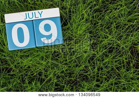 July 9th. Image of july 9 wooden color calendar on greengrass lawn background. Summer day, empty space for text.