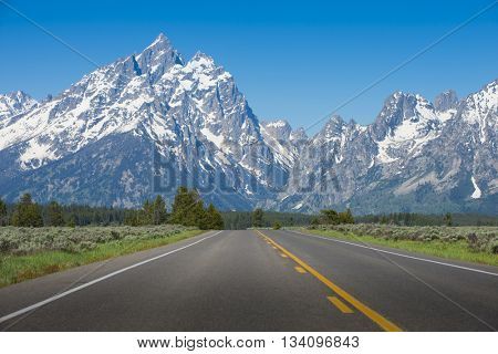 Road with one point perspective driving car to rugged rocky Teton snow capped mountain range blue sky majestic landscape scene
