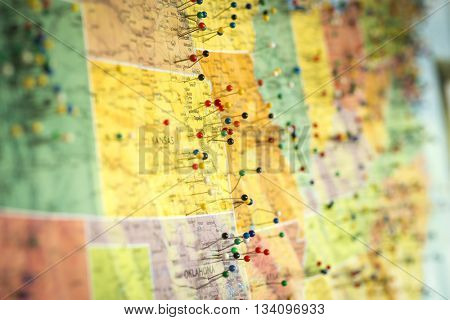 Colorful detail map macro close up with push pins marking locations throughout the United States of America