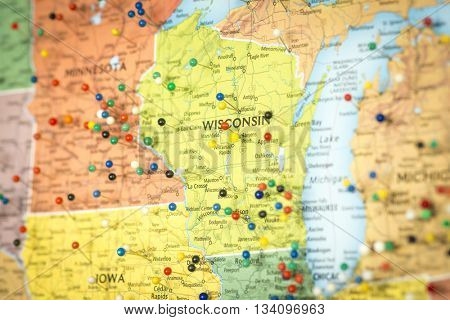 Colorful detail map macro close up with push pins marking locations throughout the United States of America WI Wisconsin