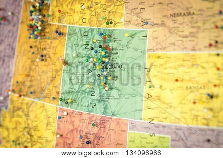 Colorful detail map macro close up with push pins marking locations throughout the United States of America Wyoming WY