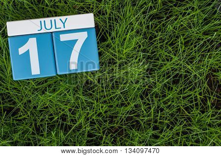 July 17th. Image of july 17 wooden color calendar on greengrass lawn background. Summer day, empty space for text.