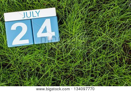 July 24th. Image of july 24 wooden color calendar on greengrass lawn background. Summer day, empty space for text.