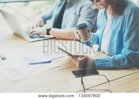 Coworkers team researching process in modern loft.Project managers working.Holding tablet female hand.Young business crew working with new startup office.Risk management process.Blurred, film effect