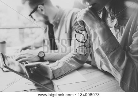 Coworkers team brainstorming process in modern office.Project manager thinking, holding glasses female hand.Young business crew working with startup studio.Laptop table, using tablet.Black White.Blurred