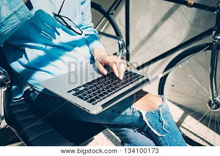 Work process modern Studio Loft.Creative Art director working coworkers office with new freelance business startup.Using Laptop, typing, holding glasses hand.Horizontal.Film effect.Blurred background