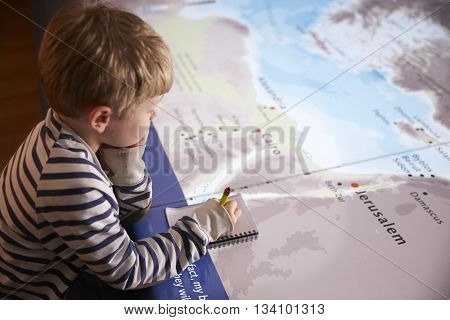Boy On Trip To Museum Looking At Map And Writing In Notebook