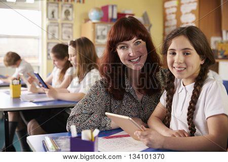 Teacher and schoolgirl using tablet computer look to camera