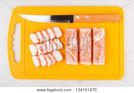 Crab Sticks And Kitchen Knife On Orange Cutting Board