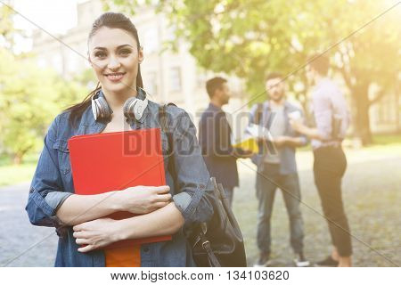 Portrait of beautiful young woman holding a book and smiling. She is looking at camera happily. Male students are standing and talking behind her near university