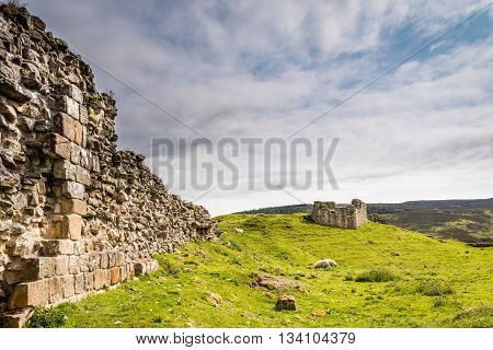 Harbottle Castle in Coquetdale, a ruined medieval site situated on a mound in the Coquet Valley, Northumberland