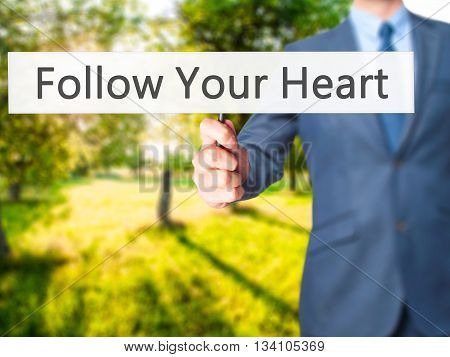 Follow Your Heart - Businessman Hand Holding Sign