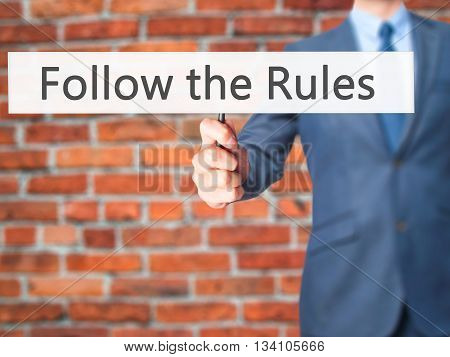 Follow The Rules - Businessman Hand Holding Sign