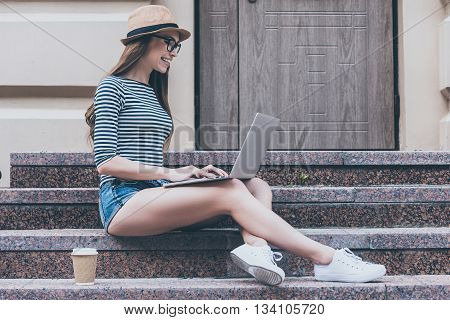 Surfing the net anywhere she wants. Side view of beautiful young smiling woman working on laptop while sitting at the staircase near her bicycle