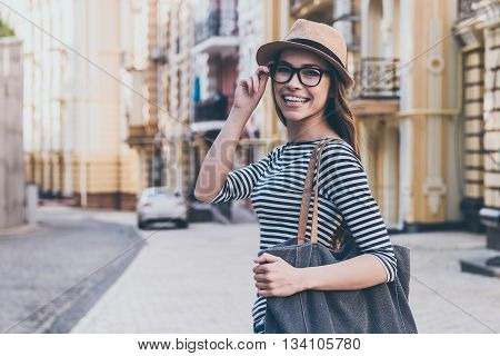 Casual beauty. Beautiful young woman with bag over shoulder looking at camera and smiling while standing outdoors