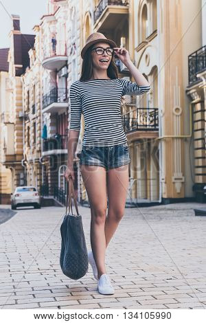 Walking along the street. Full length of beautiful young woman carrying bag and looking away with smile while walking along the street