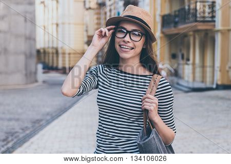 Casually beautiful. Beautiful young woman with bag over shoulder looking at camera and smiling while standing outdoors